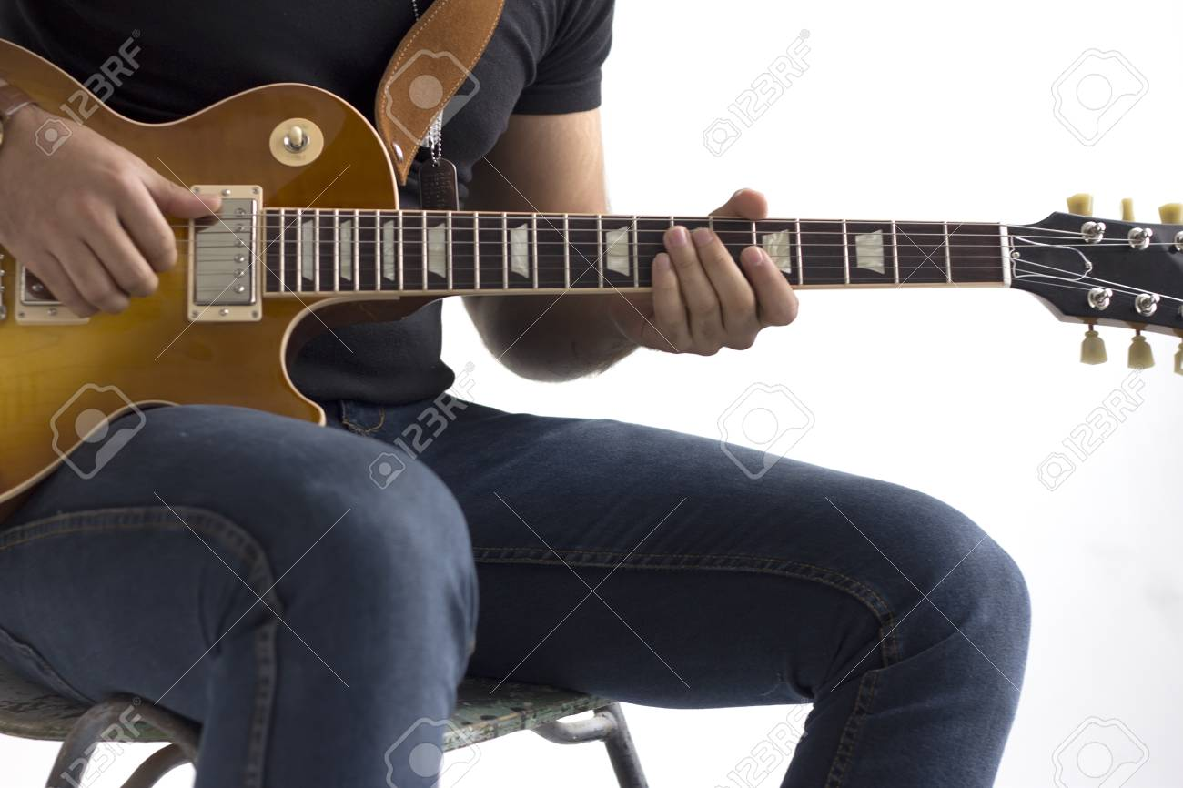 guitar playing chair desk keeps sliding down a man is sitting on and an electric white background