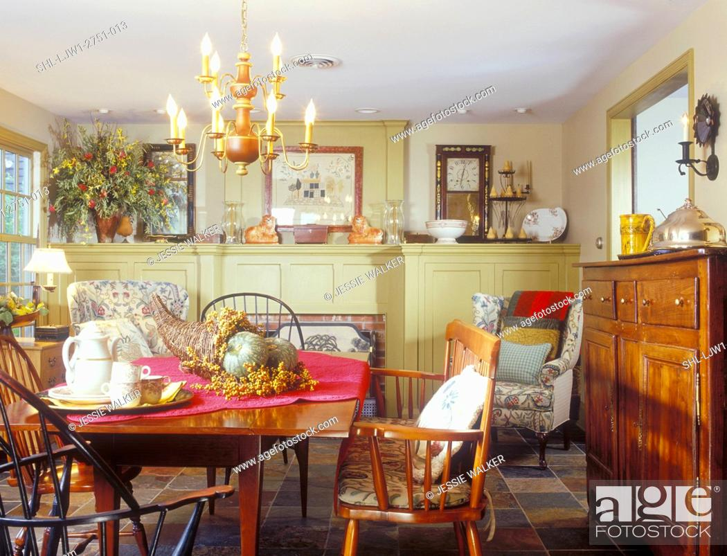 https www agefotostock com age en details photo dining rooms cherry dining table windsor chairs slate tile flooring mustard colored paneling flank fireplace concealing tv and storage shl ljw1 2751 013