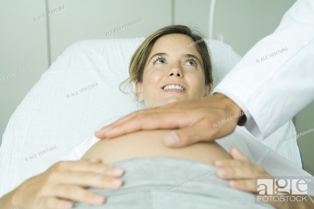 Pregnant woman lying on back in doctor's office doctor's ...