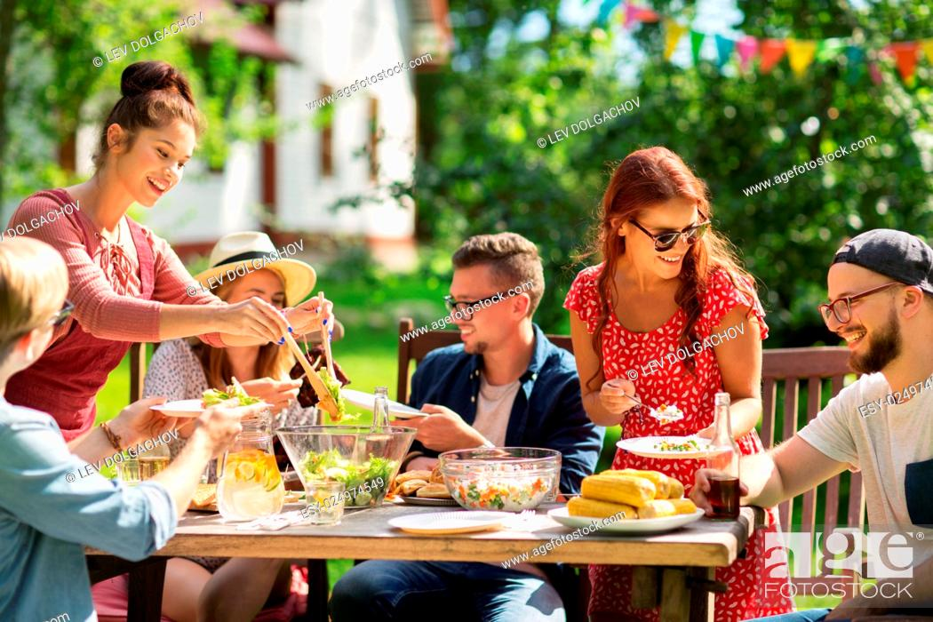 Leisure Holidays Eating People And Food Concept Happy Friends Having Dinner And Sharing Salad Stock Photo Picture And Low Budget Royalty Free Image Pic Esy 024974549 Agefotostock