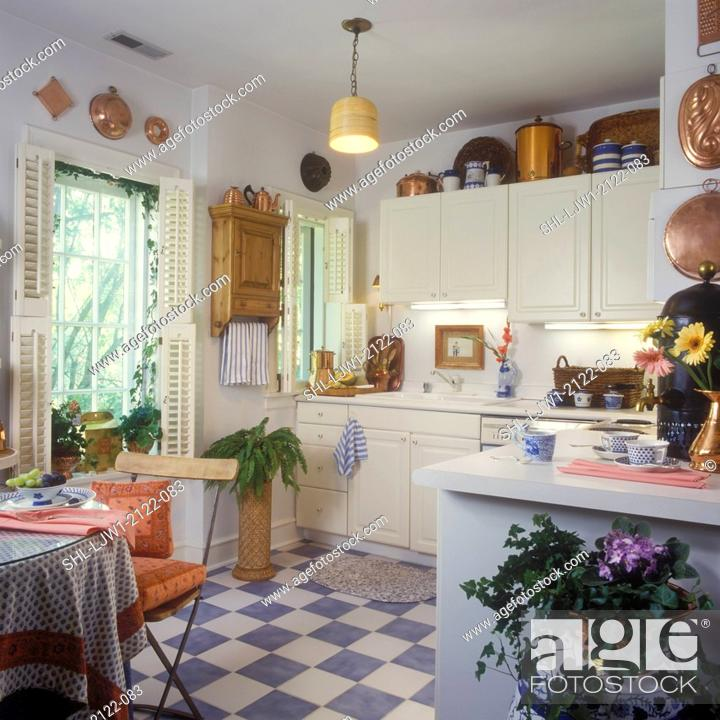 https www agefotostock com age en details photo kitchens white cabinets and counters copper collection display blue white tile floor potted plants lampshade as hanging light french country shl ljw1 2122 083