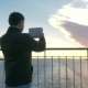 Man Using Pad To Make Scenic Photos From The Ship