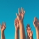Raised Hands Against Blue Sky