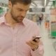 Man Using Mobile Phone In Shopping Store
