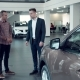 Salesman Talking To Couple Inside Car Dealership