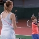 Female Tennis Instructor Teaching Boy How To Hit the Ball with a Racquet