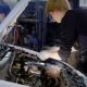 Auto Mechanic Is Disassembling an Energy Unit From Inner Structure of Car in an Dark Workshop