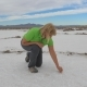 Woman Tries Salt to Taste Sitting on a White Surface of a Dry Lake in the Desert
