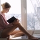 Dreaming Young Girl Read Book Sitting at Window Sill at Home. Winter Outside