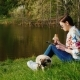 Relax with Your Favorite Dog in the Park. A Woman Uses a Tablet, Eats Fast Food