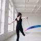 Blonde Cute Girl Doing Rhythmic Gymnastics with Colored Ribbon in Black Bodysuit