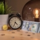 Bitcoin Fast Rising Price. View of Bitcoins, Alarm Clock and Small Bundle of Dollars on Table