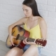 Attractive Woman Playing Guitar Near Wall