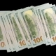 Money Becomes More on a Black Background. Winning in the Rates of Dollars