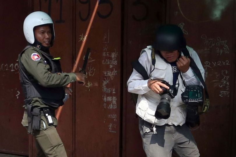 Tang Chhin Sothy, a press photographer for Agence France-Presse, is hit with a baton by a military police officer on Monday in Phnom Penh. PHOTO SUPPLIED