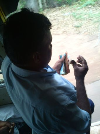 conductor counting the Rupees