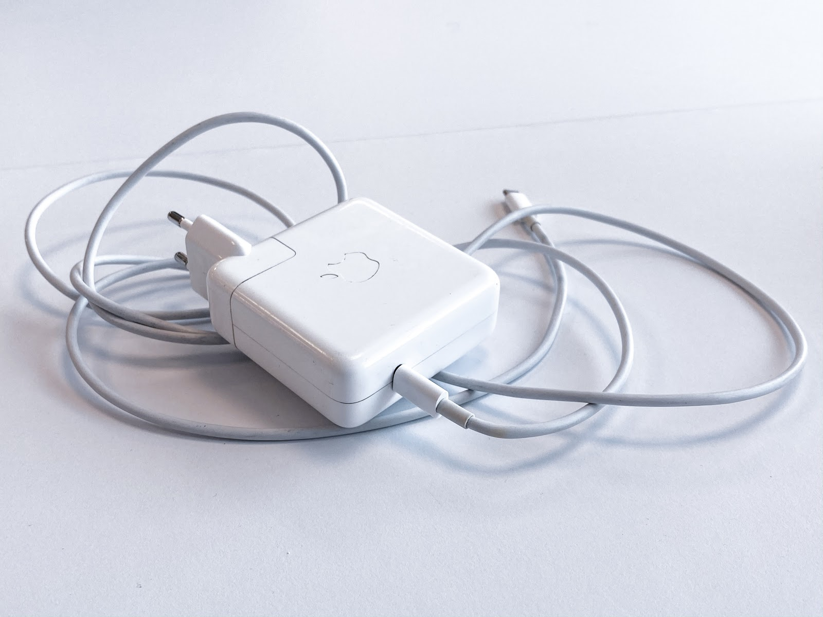 A white Apple laptop charger with cord curled up beneath it.