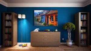 Room with electric blue walls, bookshelves, a plant, a lamp, a dresser and a painting
