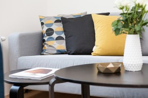 Black table in front of a gray sofa with three colorful pillows