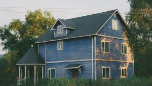 A blue suburban house with three stories.