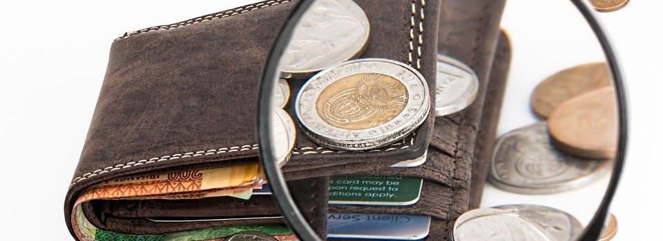 a view of a wallet and some money through a magnifying glass