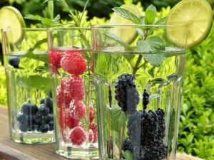 Glasses with water and fruits as a refreshment during a hot summer day