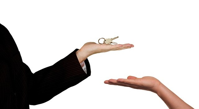 One person giving some keys to another.