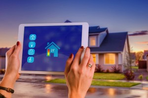 A person using a tablet to connect the smart house to an application and this is something that will attract millennial home buyers as well.