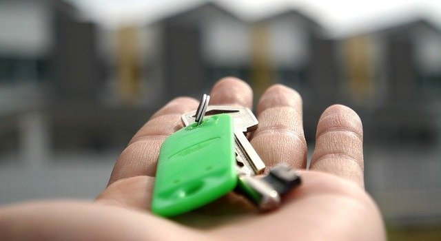 A person giving keys to the new owner after investing in luxury real estate has come to its end.