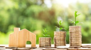 Piles of money and a small wooden model house because saving money is one of the real estate trends in Texas