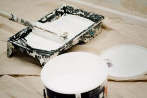 A painting brush and a can with white paint.