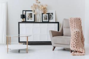 There is a beige armchair next to a small table, and a black and white cabinet- a perfect stylish yet simple decor idea for your NYC apartment.