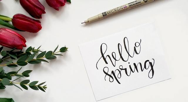 There is a piece of paper saying Hello spring, and there are some flowers all around it.