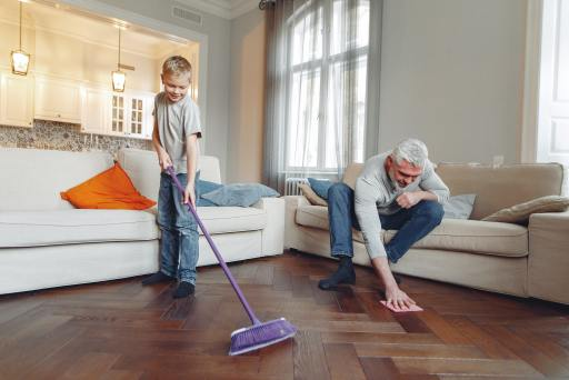 Man and a boy cleaning the wooden floor