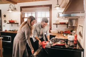 A man and a woman in the kitchen  cooking and smiling