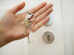A man holding an apartment key after he manages to buy an apartment out of state.