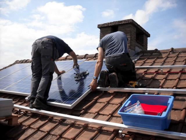installateurs zijn zonnepanelen aan het leggen op een schuin dak