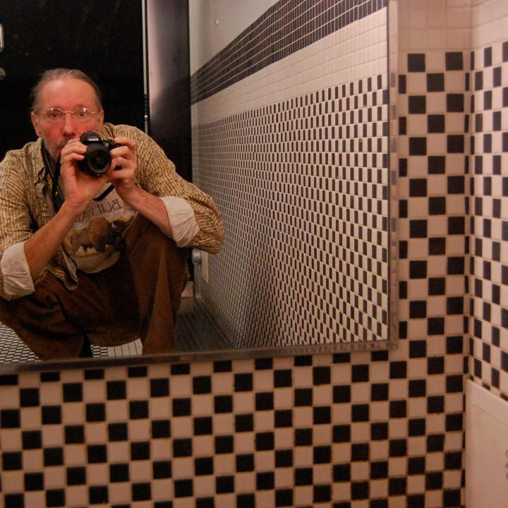 Photographer self-portrait in the mirror of a bathroom with checkered tiles