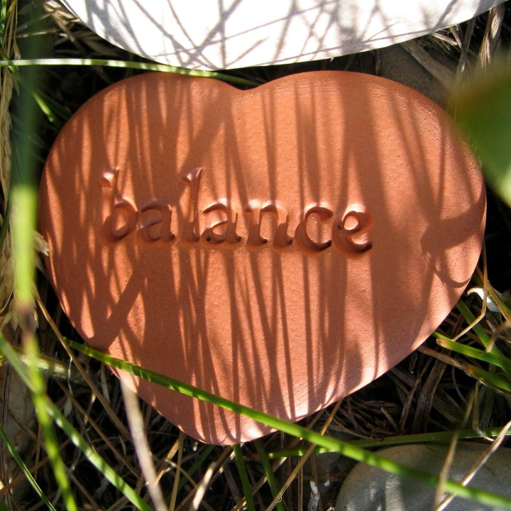 """A ceramic heart with the word """"balance"""" written on it"""