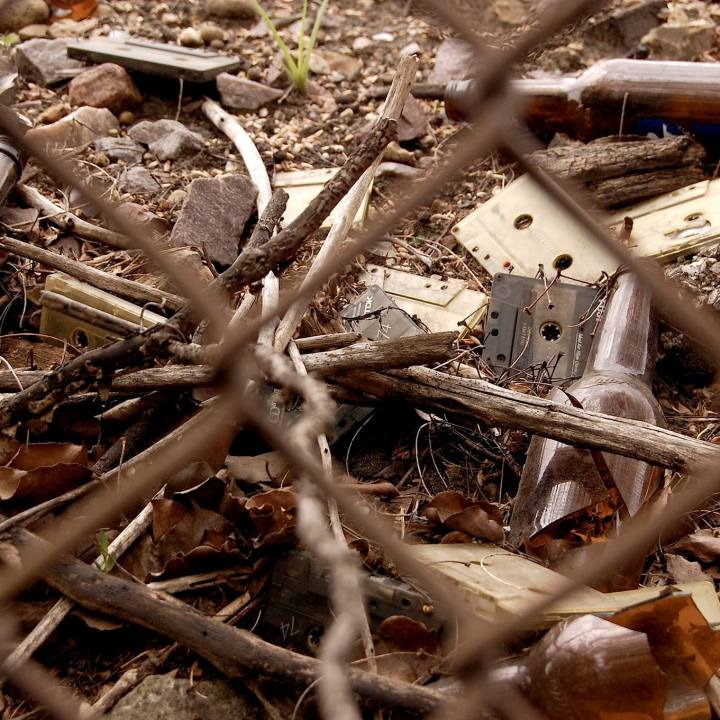 Cassettes and broken bottles on the ground behind a chain link fence