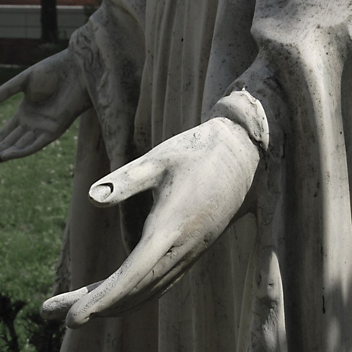 Hands of a statue of The Blessed Virgin Mary, one in light, one in shadow