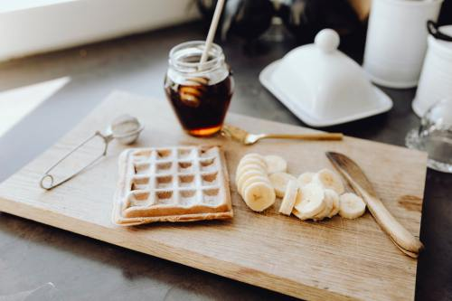 waffle, sliced bananas, and a jar of honey on a wooden cutting board
