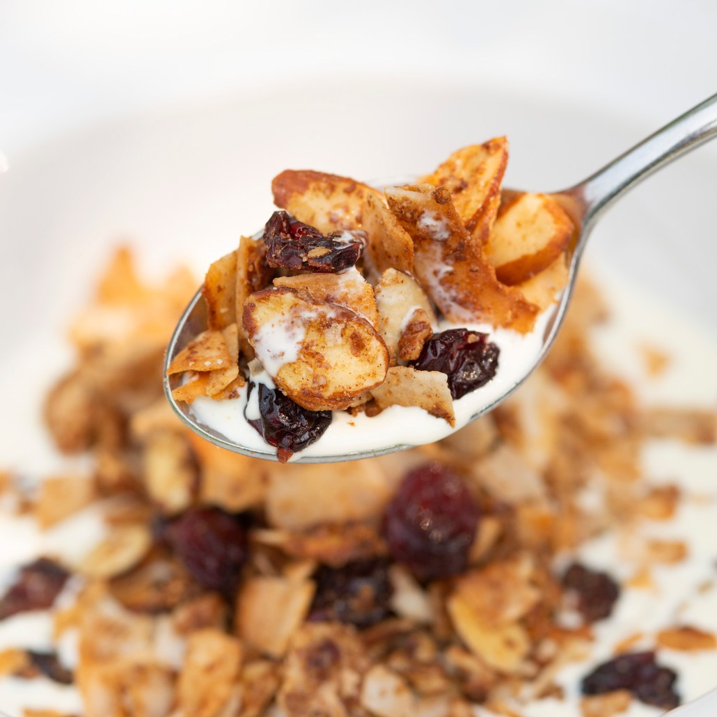 photo of a bowl of granola with a spoon full of granola hovering above