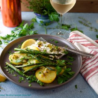 A picture showing a baked cod fish fillet, with a side of potatoes and asparagus.