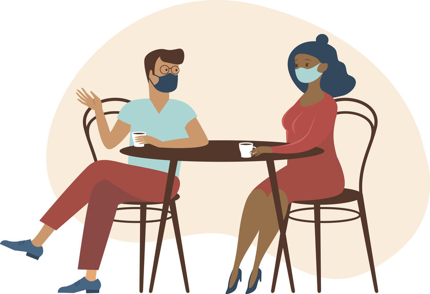 couple wearing protective medical masks sitting at table,