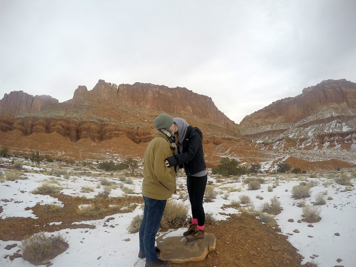 a couple kisses while in front of scenery at Capitol Reef National Park