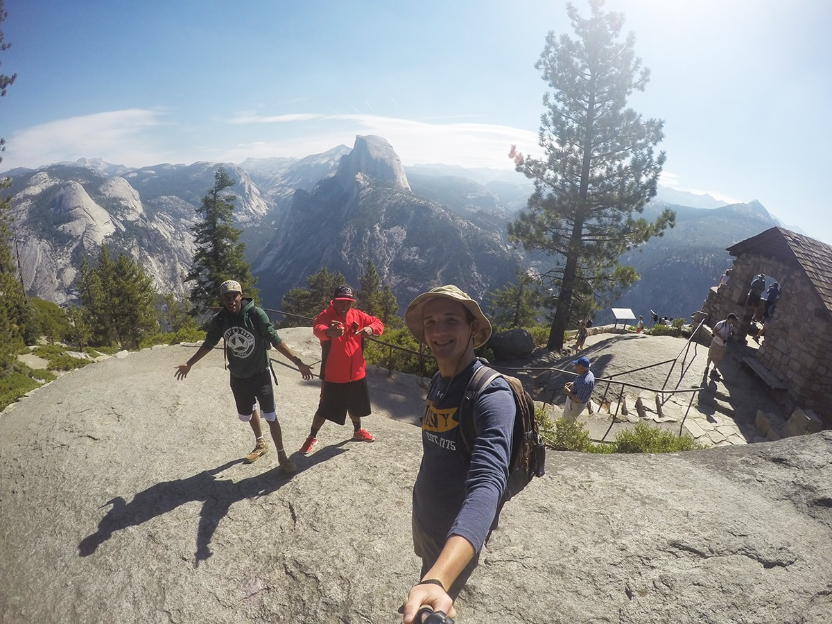 3 men pose from the viewpoint of Glacier Point in Yosemite National Park California
