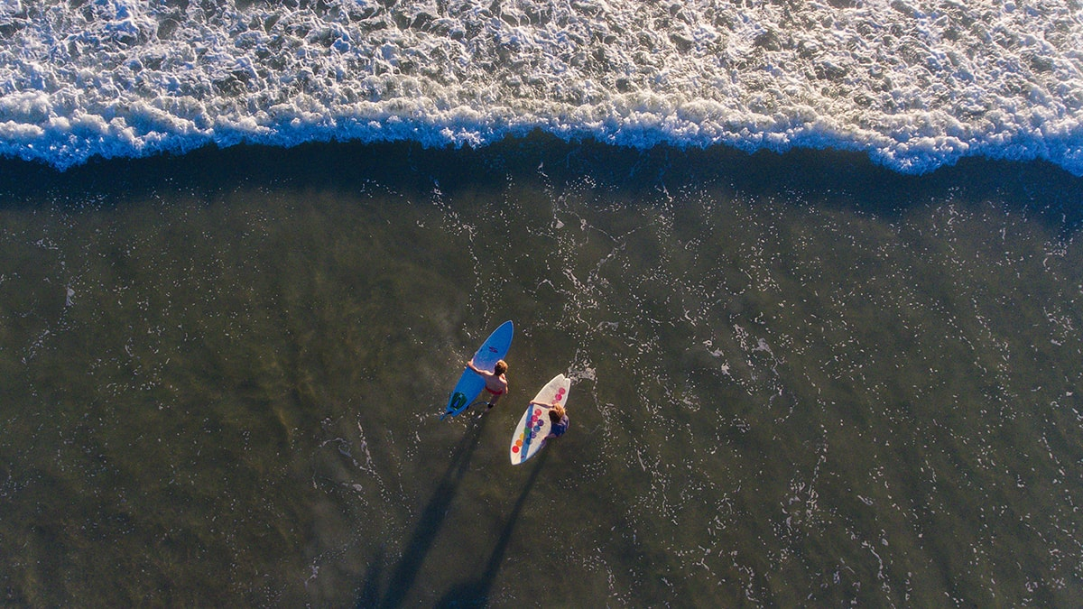 Two surfers going into the ocean at Jacksonville Beach, Florida