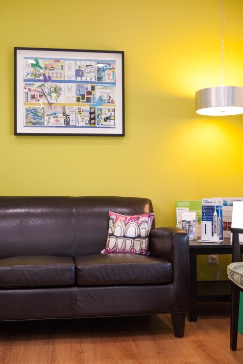 Waiting area with leather sofa, green walls, and throw pillow with artistic tooth pattern