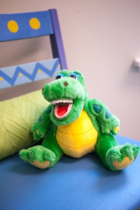 Children's stuffed alligator toy on brightly painted chair